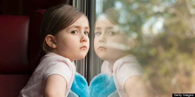 Young girl staring out of a window, with her mirror image reflecting back at her.