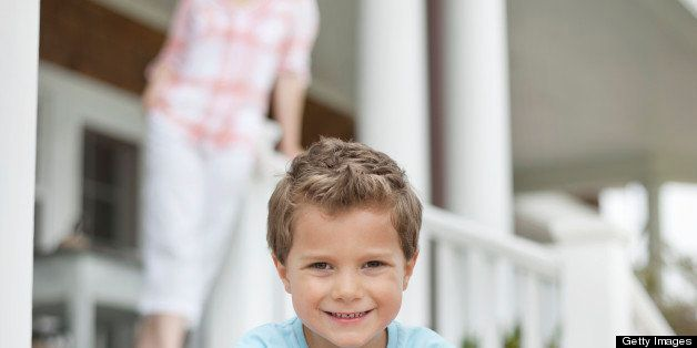 Boy sitting on porch, smiling