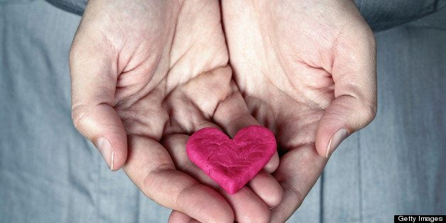 Woman holding the cracked pink heart in her hands. Saving love concept. Giving Heart.
