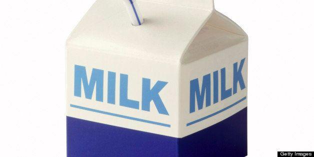 Milk carton with straw on white