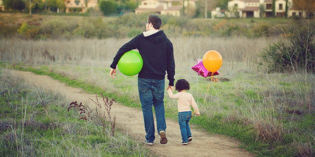 Father holding his little girl's hand as they walk together along a country trail. There are suburban homes in the background. She has colorful balloons.