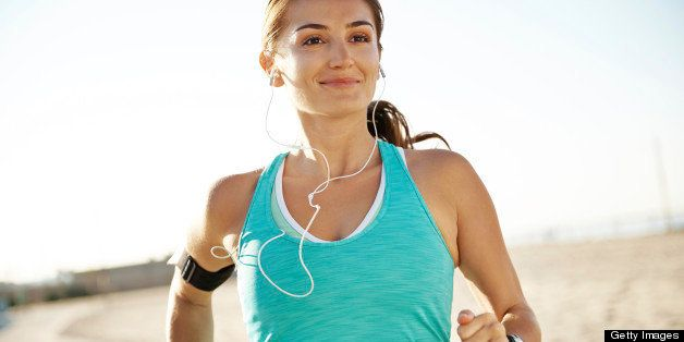 A beautiful athletic woman running along a footpath at a beach