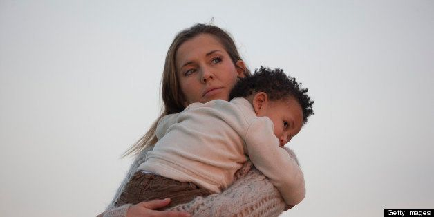 Woman holding her son at sunset