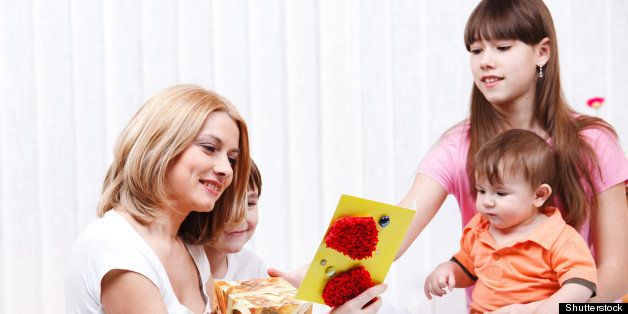 Mother reading greeting card her children presented