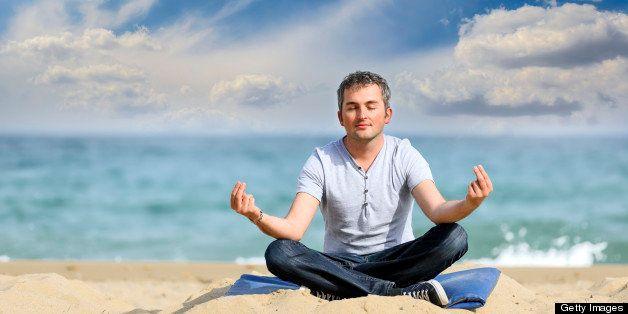 peaceful man making yoga on beach.