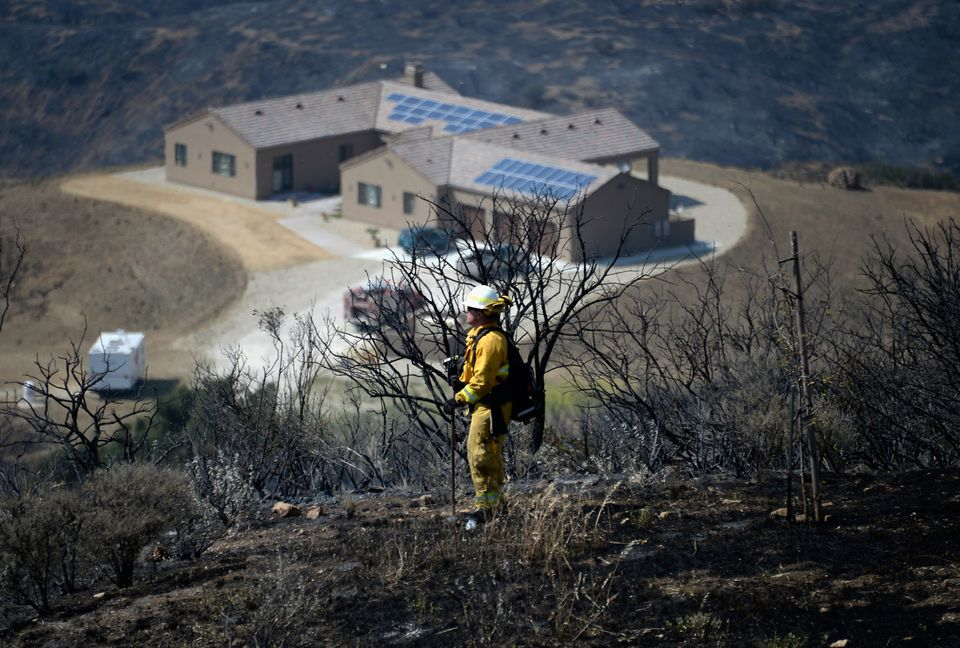 MALIBU, CA - MAY 04:  A firefighter keeps a lookout for hot spots in the charred landscape around a home which escaped damage