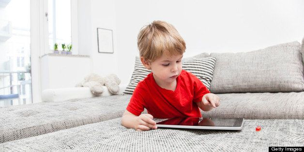 a Two year old boy playing with a digital tablet Pc at home on the couch