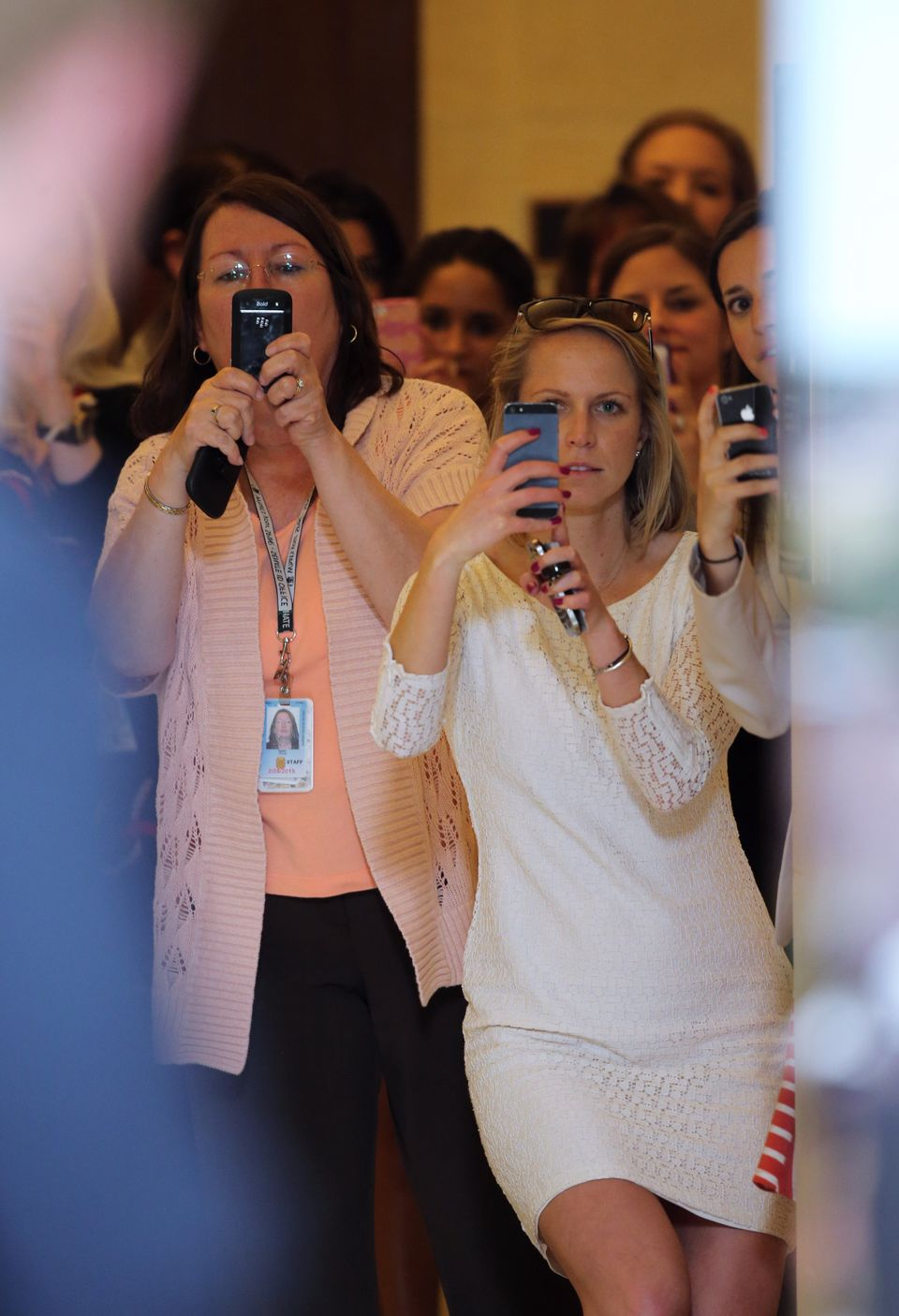 WASHINGTON, DC - MAY 09:  Women watch and take camera phone pictures as HRH Prince Harry tours an anti-landmine photography e