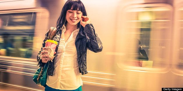New Yorker girl enjoying in the subway with music and coffee against a train.