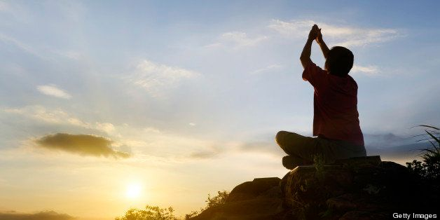 Man with yoga sitting pose in silhouette in outdoor.