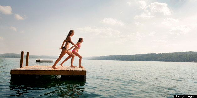 Two Girls Jumping Of Floating Dock