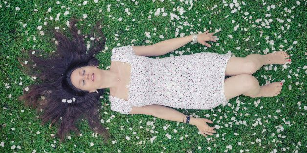 Young woman in a meadow full of apple petals - from above - image cross processed