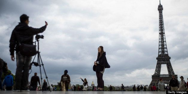 Tourists take picture of the Eiffel Tower, on Trocadero Square, on May 14, 2013 in Paris. Paris's image, already tarnished by