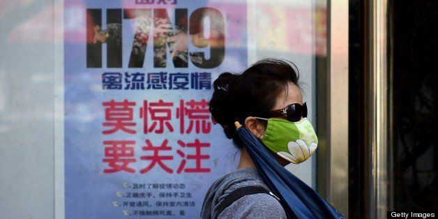 A woman wears a face mask as she walks past a poster showing how to avoid the H7N9 avian influenza virus, by a road in Beijin