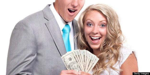 Beautiful wedding couple on white background holding 50 and 20 dollar bills (U.S. Currency)
