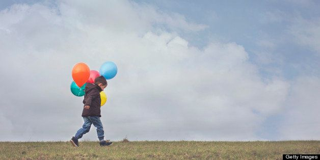 A young boy carrying his colourful birthday balloons through a field in North Yorkshire, England. Negative Space