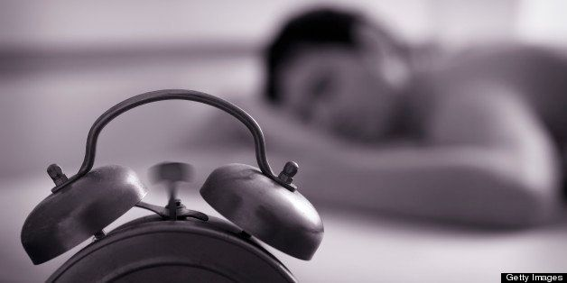 Naked man sleeping. Focus on alarm clock, ringing