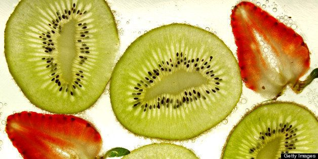 Sliced kiwi fruit and strawberries against bubbles.