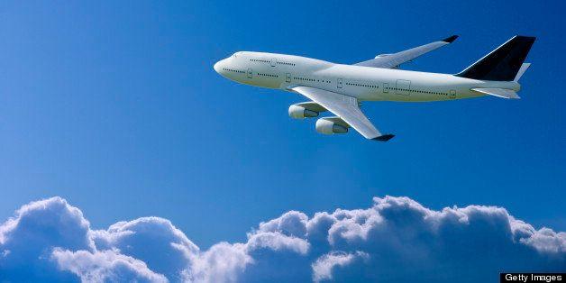 Commercial jetliner flying over clouds.