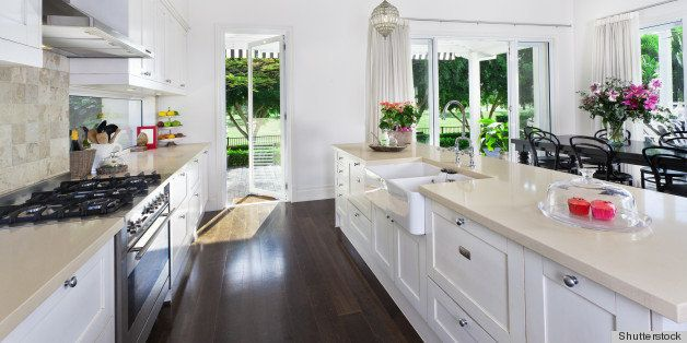 Stylish open plan kitchen with stainless steel appliances and dining area overlooking a pool and golf course
