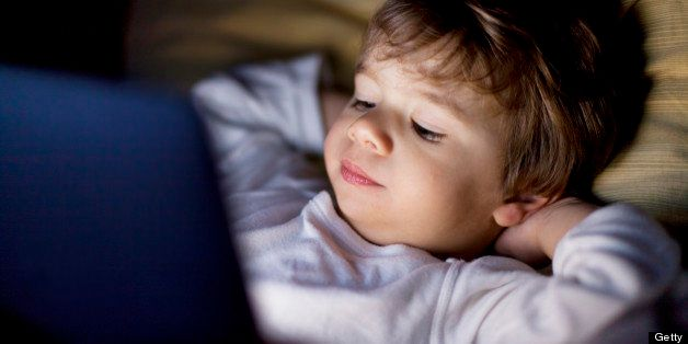 Small boy looking at a tablet in the dark