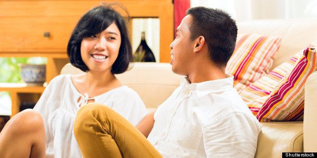 asian couple in their living...