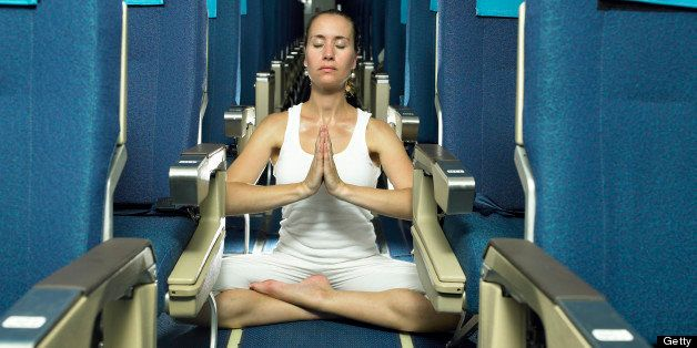 Woman meditating in aisle of airplane