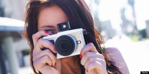 A brunette standing in a urban setting holding a camera in front of her face and taking a picture