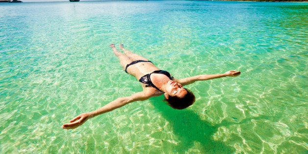 Young woman floating and relaxing backstroke in tropical water of Caribbean, St. Thomas U.S. Virgin Islands.