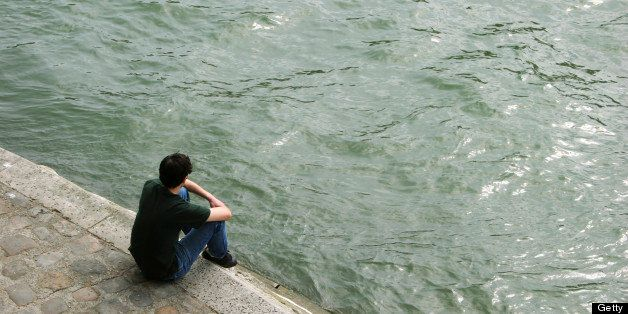 a guy sitting on the edge of the seine
