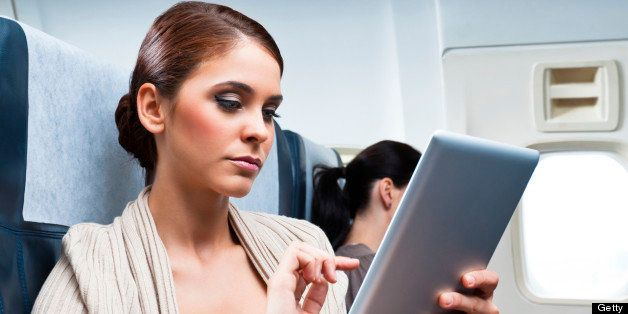 Young woman sitting on the airplane and using a digital tablet.