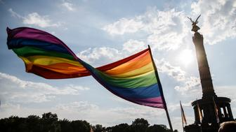BERLIN, GERMANY - JULY 28: A participant waves a rainbow- colored flag in the final of the 40th Christopher Street Day gay pride march in front of the landmark Siegesslaeule on July 28, 2018 in Berlin, Germany. Known as CSD, the event attracts thousands of people every year. This parade takes place for the 40th time this year. (Photo by Carsten Koall/Getty Images)