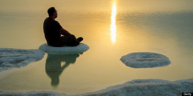 A man sitting and meditating on a salt formation in the dead sea at sunrise.