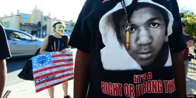 A man wears a single bullet around his neck over his Trayvon t-shirt as people hold placards and shout slogans during a rally in Los Angeles in the aftermath of George Zimmerman's acquittal in the shooting death of Florida teen Trayvon Martin,  on July 15, 2013 in California, where local civil rights activists and other leaders urged participants to remain peaceful as they express frustration with the trial's outcome. AFP PHOTO/Frederic J. BROWN        (Photo credit should read FREDERIC J. BROWN/AFP/Getty Images)