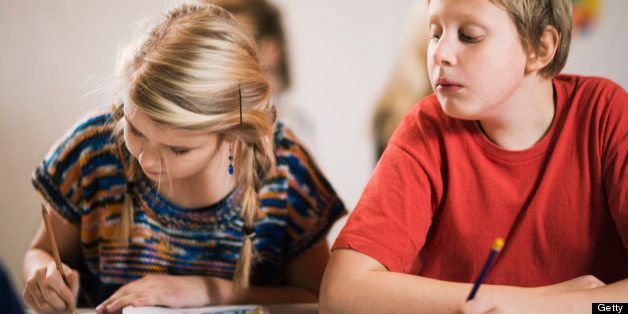 Schoolboy having a peep at what his classmate is writing Sweden.
