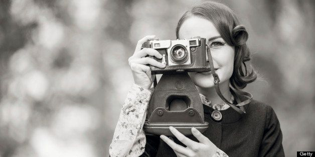 Retro style woman portrait outdoors using a vintage camera