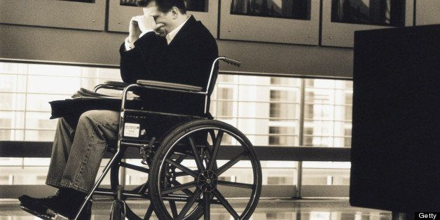 Businessman sitting in wheelchair at airport (B&W sepia tone)