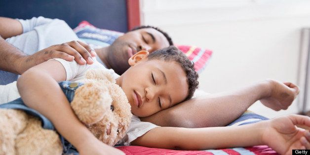 Father and son with stuffed toy sleeping in bed
