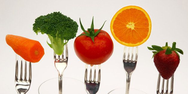 Five fresh fruits and vegetables, part of the daily recommended  healthy diet, held on the prongs of forks, on a white background.