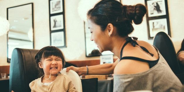 Pretty young mom and toddler having fun playing on the dining table in a restaurant joyfully.