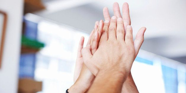Closeup of hands giving a group high-five