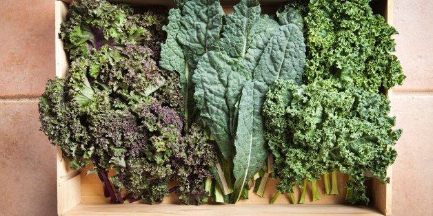 Subject: Several varieties of kale in a wood crate freshly harvested from a garden. Including Lacinato Kale, red Kale, and Green Kale.