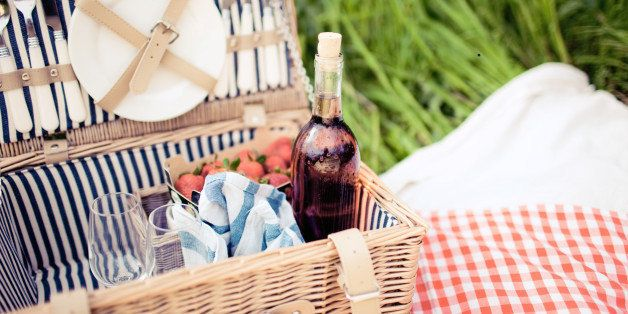 Picnic basket with rose, glasses, strawberries and dishes in meadow.