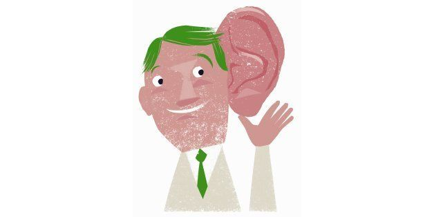Smiling businessman listening with enormous ear