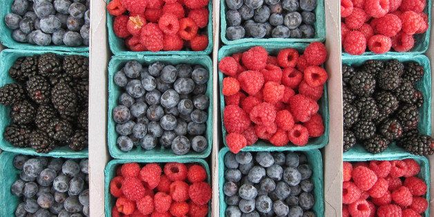 Overhead view of alternating baskets of blueberries, raspberries, and blackberries on display at local farmers market.