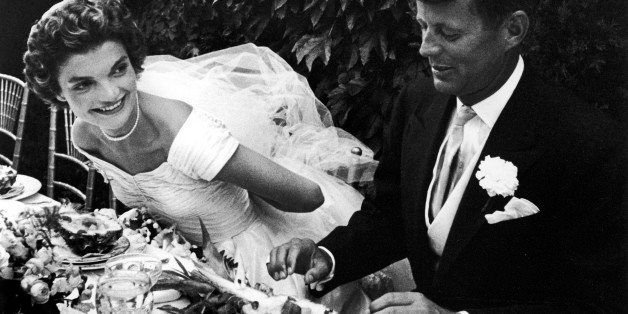 NEWPORT, UNITED STATES - SEPTEMBER 01:  Senator John Kennedy and bride Jacqueline sitting together outdoors at table, eating pineapple salad ,at their wedding reception.  (Photo by Lisa Larsen/Time & Life Pictures/Getty Images)