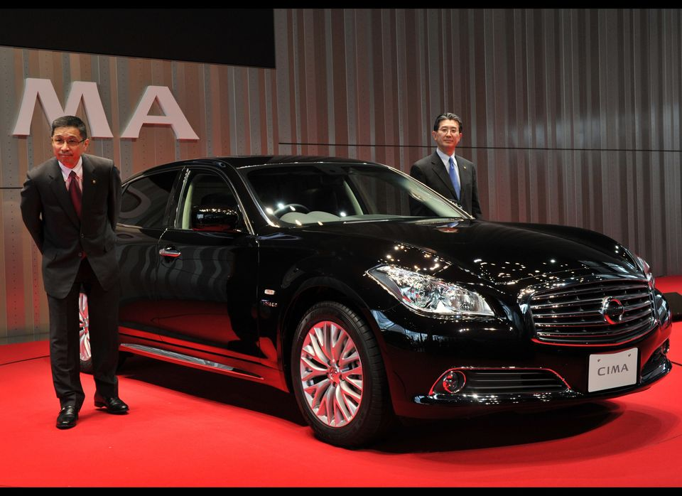Japan's auto giant Nissan Motor executive vice president Hiroto Saikawa (L) displays the company's new luxury sedan 'Cima', w