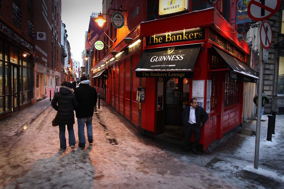 <em>Caption: Shoppers pass a pub called The Bankers on December 1, 2010 in Dublin, Ireland. (Photo by Peter Macdiarmid/Getty