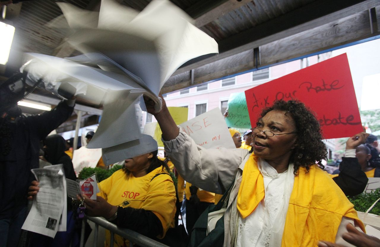 Carmen Edwards waves her mortgage papers during a demonstration outside JPMorgan Chase's annual shareholder meeting in downtown Manhattan on May 18, 2010. Edwards said the bank was attempting to foreclose on her home.