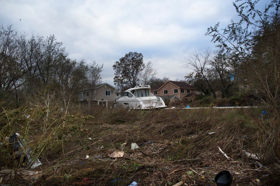A yacht rests beside two homes after it was driven inland by flood waters, Wednesday, Oct. 31, 2012, in the Staten Island bor